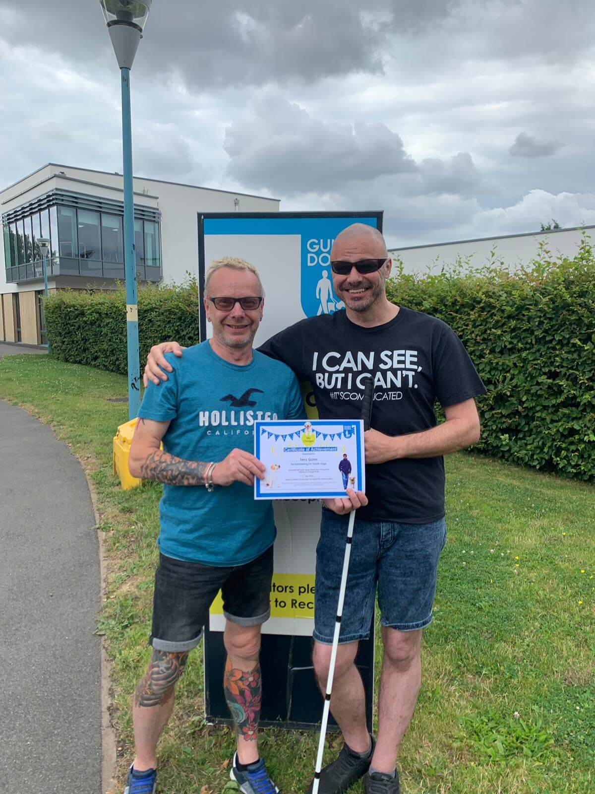 Receiving our certificate of achievement for fundraising for Guide Dogs UK. Two men, one sighted and the other one blind standing in front of The Guide Dogs UK sign. Holding up a certificate of achievement for fundraising for The Guide Dogs UK.